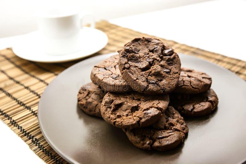El hogar delicioso hizo las galletas de microprocesador de chocolate en una placa marrón imagen de archivo libre de regalías
