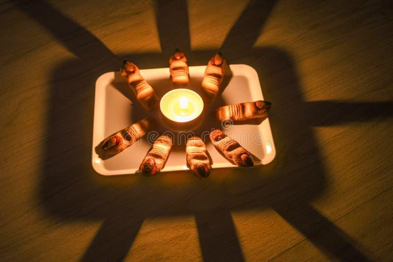 El hogar hecho recientemente apoyó las galletas del finger de la bruja de Halloween en una placa con la vela en el centro imágenes de archivo libres de regalías