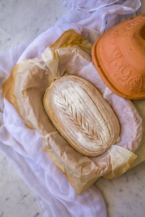 El hogar hizo al artesano amargo de la pasta deletreó el pan en la fabricación en una cacerola antes de cocer en el fondo de márm imagen de archivo libre de regalías