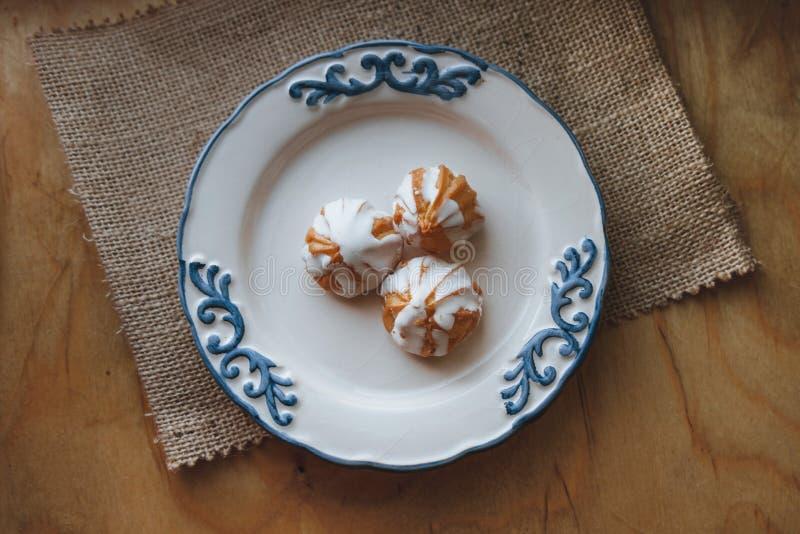 El hogar hizo la crema de los choux en la placa blanca Sobre en la tabla de madera Visión superior con un esmalte blanco En fondo foto de archivo libre de regalías