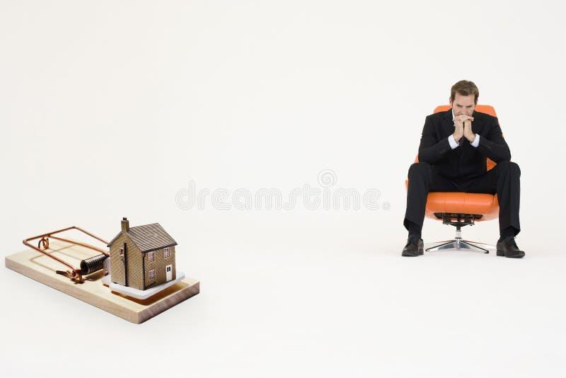El hogar modelo en trampa del ratón con el hombre de negocios preocupante que se sienta en la silla que representa las propiedades foto de archivo libre de regalías