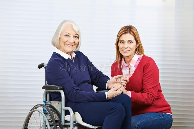 El holdind de los jóvenes y de la mujer mayor da junto foto de archivo libre de regalías