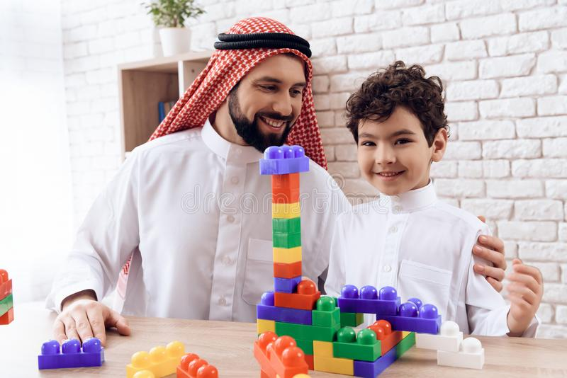 El hombre árabe con el niño pequeño construye la torre de bloques plásticos coloreados imagen de archivo