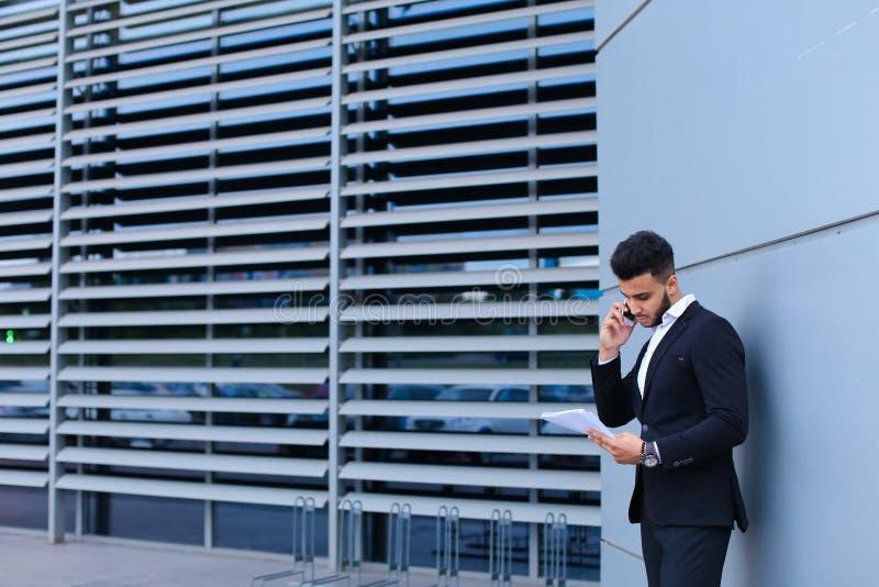 El hombre árabe hermoso habla en el teléfono móvil en centro de negocios fotos de archivo libres de regalías