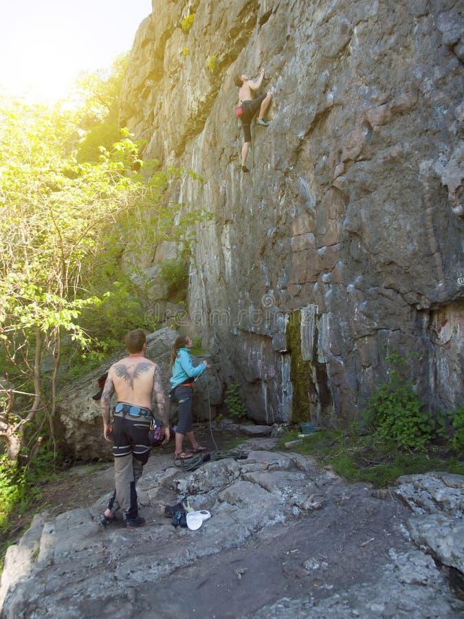 El hombre útil sube en una roca con el apoyo de amigos fotos de archivo