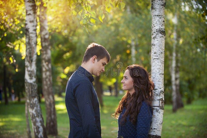 El hombre abraza a la muchacha en un paseo en el parque del otoño imagenes de archivo