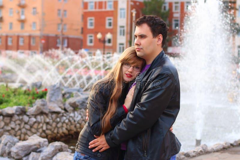 El hombre abraza a la mujer en la chaqueta de cuero cerca de la fuente fotos de archivo libres de regalías
