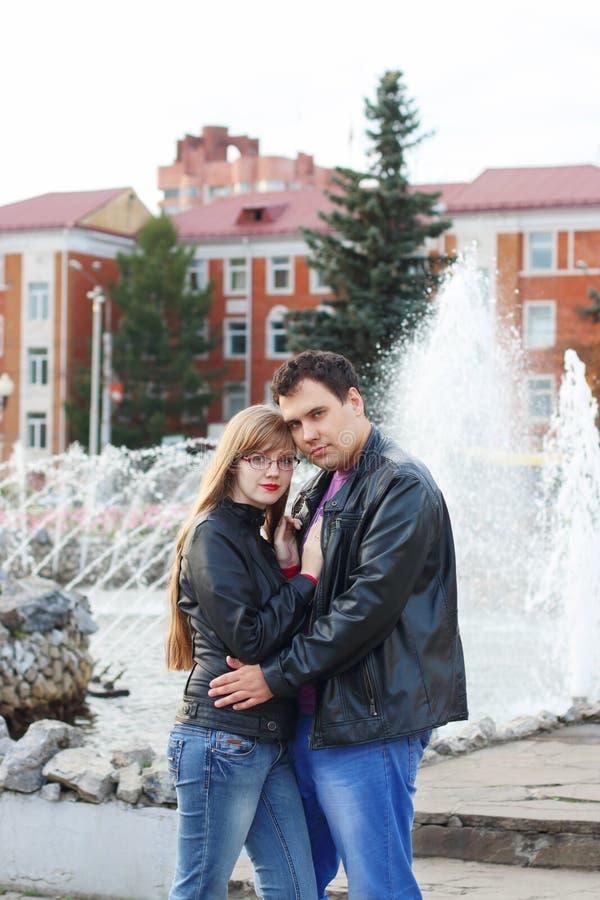 El hombre abraza a la mujer en las chaquetas de cuero cerca de la fuente fotografía de archivo libre de regalías