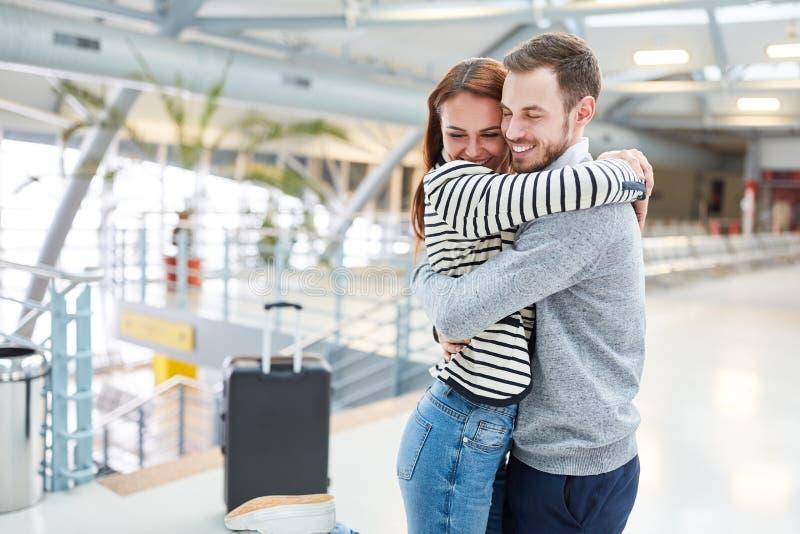 El hombre abraza a su esposa en la reunión en el terminal fotos de archivo