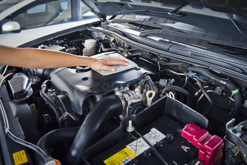 El hombre abre la capilla del coche y el coche de pulido con el paño de la microfibra fotos de archivo