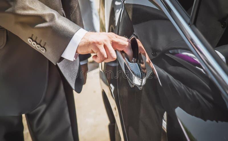 El hombre abre una puerta de coche imagen de archivo