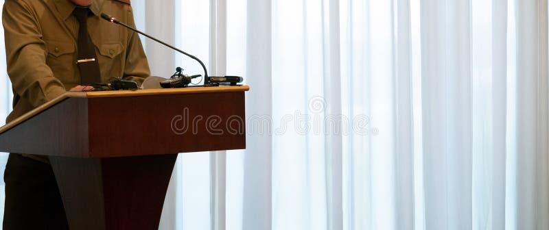 El hombre abstracto en una camisa verde se coloca en el podio delante de un micrófono Primer Copie el espacio Discurso del concep foto de archivo