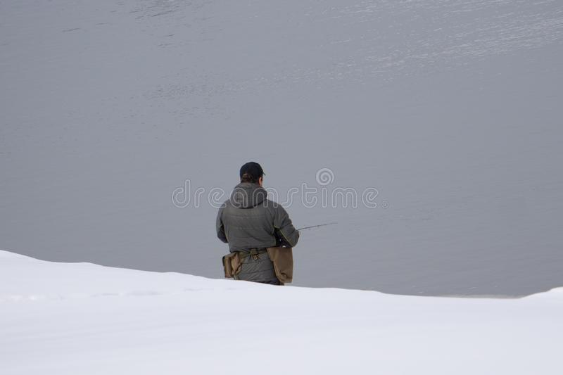 El hombre activo está pescando en el mar del control rocoso del pescador de la costa que empuja cebo en la línea, prepara la barr fotografía de archivo libre de regalías