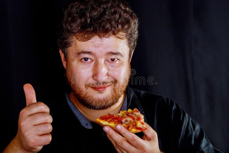 El hombre adentro toma a las manos apetitosas toma un pedazo de pizza delicioso imagen de archivo