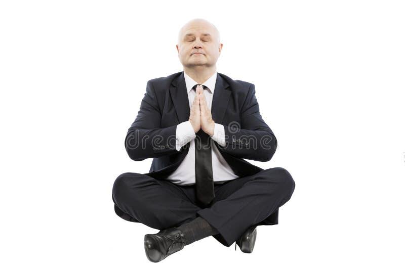 El hombre adulto calvo en un traje en la posición de loto ruega Aislado en un fondo blanco imágenes de archivo libres de regalías