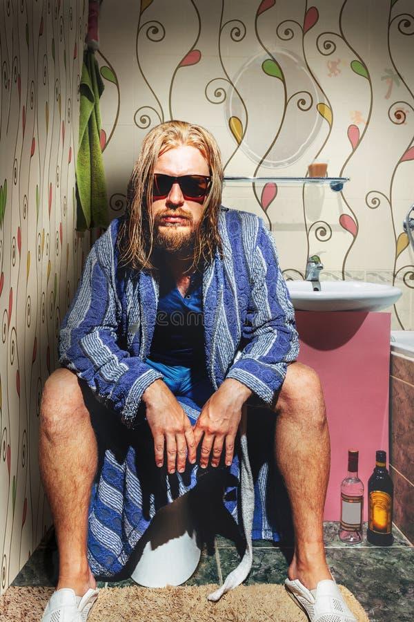 El hombre adulto con una barba, vidrios que llevan y un traje, se sienta en el cuarto de baño y mira en la cámara fotos de archivo