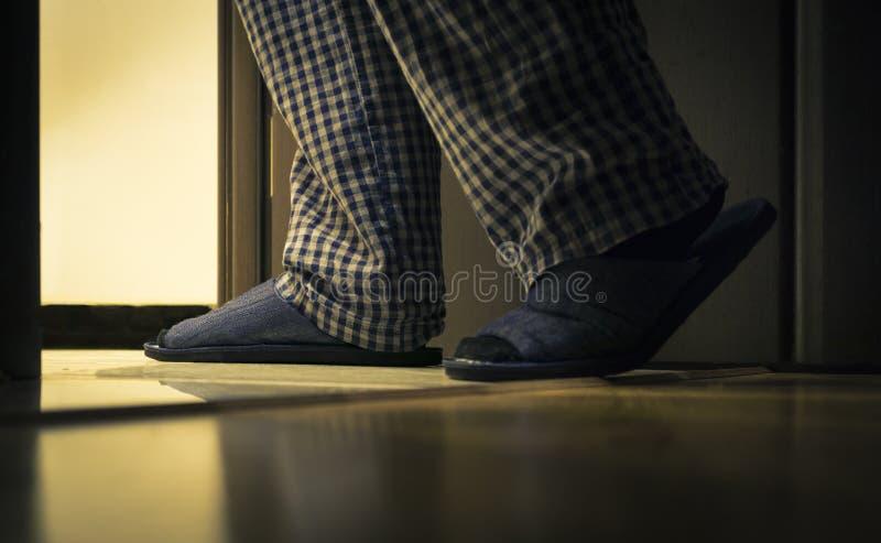 El hombre adulto en pijamas camina a un cuarto de baño en la noche Concepto de las saludes del ` s de los hombres imagenes de archivo