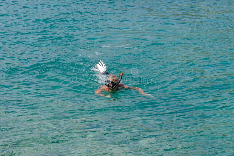 El hombre adulto, pensionista est? buceando en las aguas de la turquesa del mar adri?tico Anciano sana que disfruta del d?a de ve imagen de archivo libre de regalías