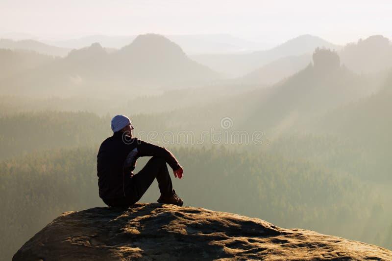 El hombre adulto que sube en la cima de la roca con la vista aérea hermosa del valle brumoso profundo grita foto de archivo libre de regalías