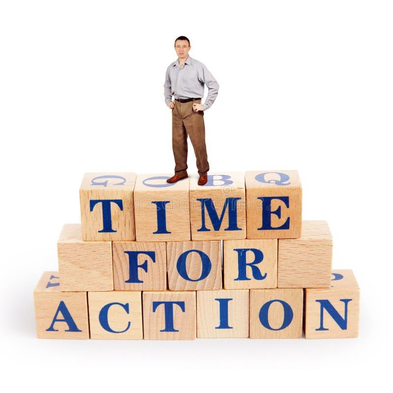 El hombre adulto se coloca sobre un montón de bloques de madera con un rato de llamada para la acción imagenes de archivo