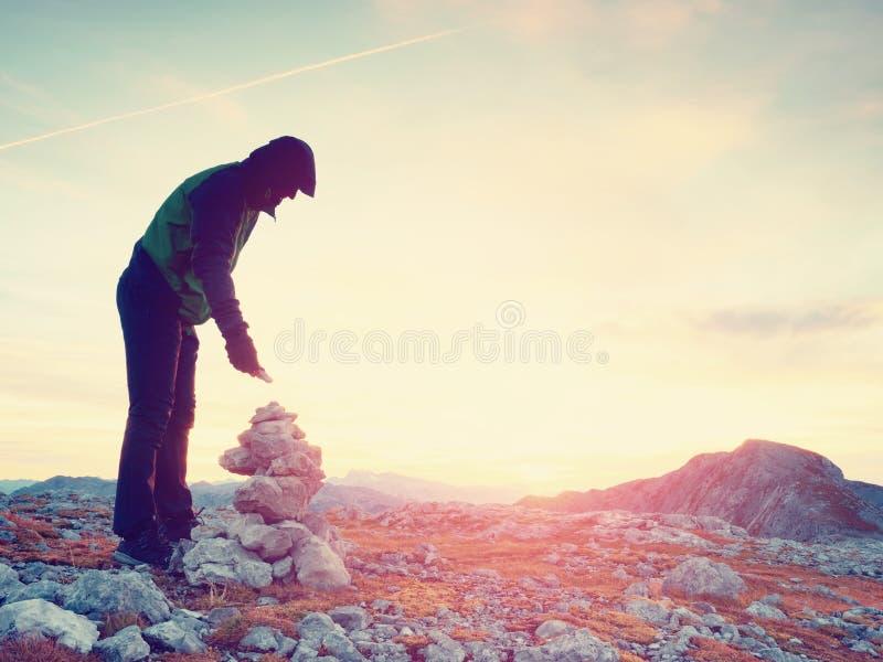 El hombre adulto solo está almacenando la piedra a la pirámide Cumbre de la montaña de las montañas, igualando el sol en el horiz foto de archivo