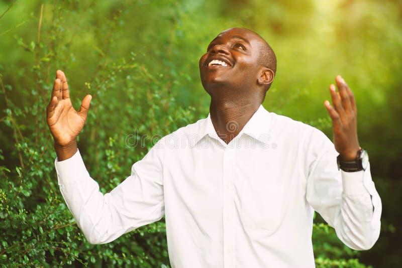 El hombre africano de la sonrisa que ruega para agradece a dios foto de archivo