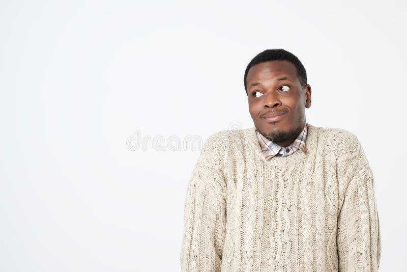el hombre africano en suéter encoge hombros con la confusión foto de archivo
