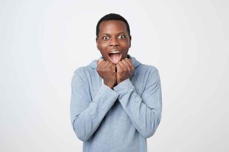 El hombre africano feliz afortunado como el ganador aprieta los puños, disfruta triunfo foto de archivo