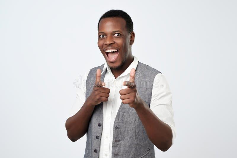 El hombre africano hermoso joven con dos armas de las manos firma gesto que señala en usted la cámara imagenes de archivo
