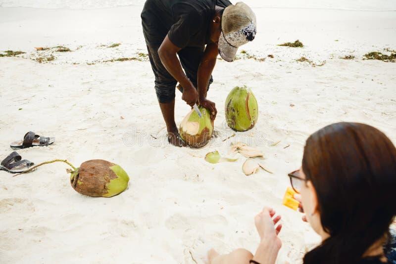 El hombre africano pela el coco para el turista femenino en la playa foto de archivo libre de regalías