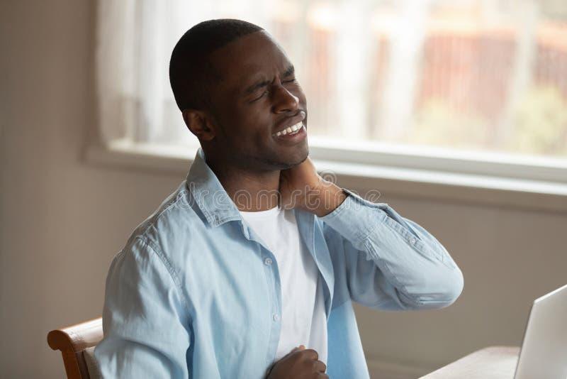 El hombre africano que frunce el ceño dando masajes al nervio pellizcado siente dolor en cuello imágenes de archivo libres de regalías