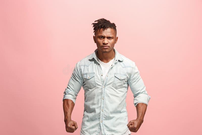 El hombre afro enojado emocional joven que grita en fondo rosado del estudio foto de archivo libre de regalías