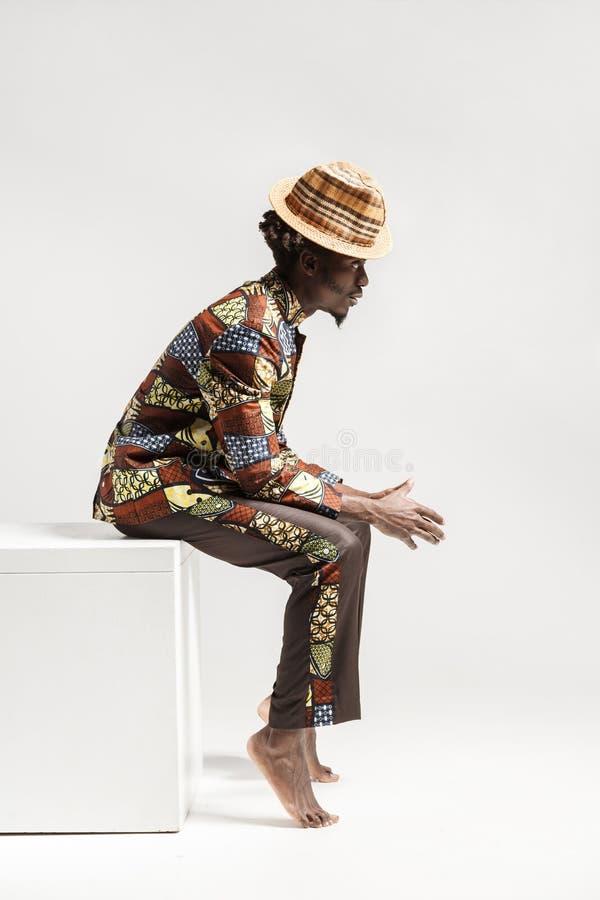 El hombre afro infeliz en ropa tradicional se sienta en coub fotos de archivo