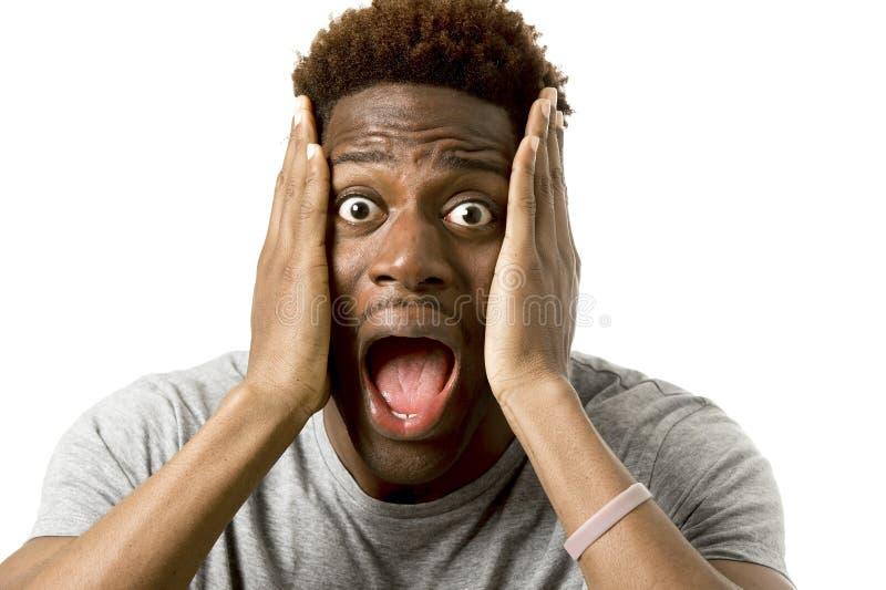 El hombre afroamericano atractivo joven desesperado en choque con la boca abierta se preocupó fotografía de archivo