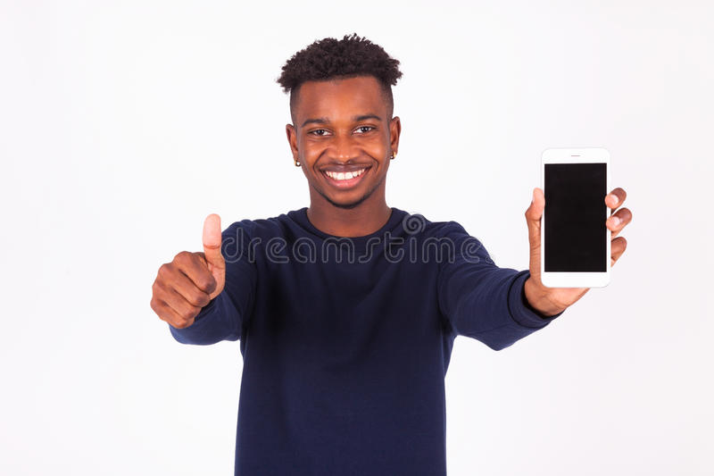 El hombre afroamericano joven que lleva a cabo smartphonemaking manosea con los dedos para arriba foto de archivo