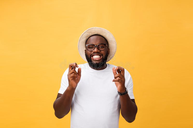 El hombre afroamericano joven sobre los fingeres que cruzaban sonrientes aislados del fondo con esperanza y los ojos se cerró Sue imágenes de archivo libres de regalías