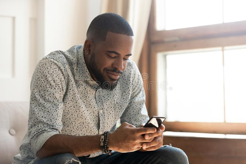 El hombre afroamericano joven usando el app del smartphone se sienta en el sofá imagen de archivo