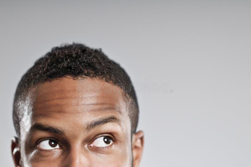 El hombre afroamericano observa solamente la mirada para arriba y lejos fotografía de archivo libre de regalías