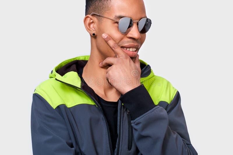 El hombre afroamericano que sonríe y que presenta para el anuncio lleva las gafas de sol de moda del espejo, en la pared blanca c imagenes de archivo