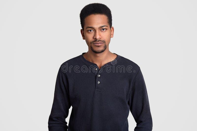 El hombre afroamericano serio vestido en suéter casual, tiene expresión segura de sí mismo, mira directamente la cámara, aislada  imagen de archivo libre de regalías