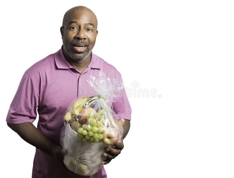El hombre afroamericano sostiene alegre una cesta de fruta en el fondo blanco fotografía de archivo