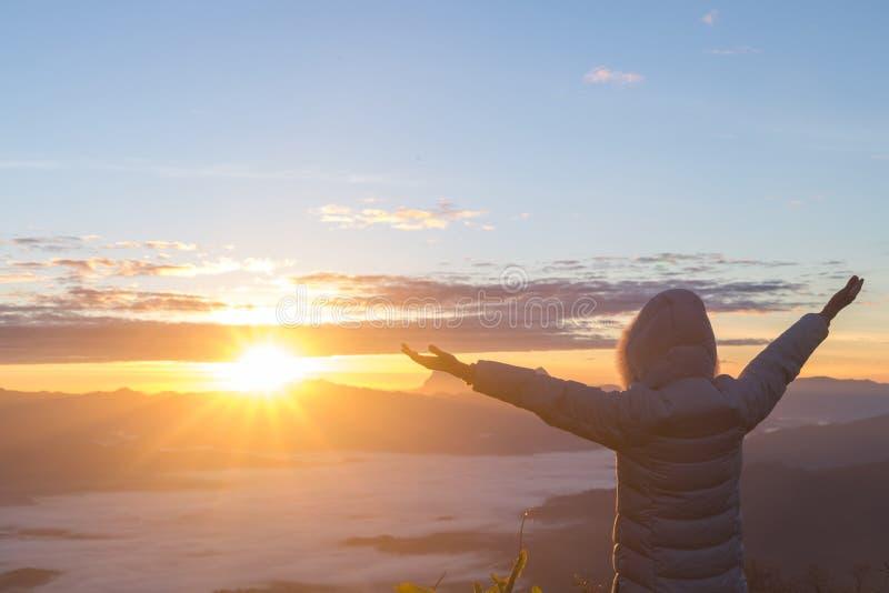 El hombre agradece a dios en la montaña en la salida del sol por la mañana foto de archivo libre de regalías