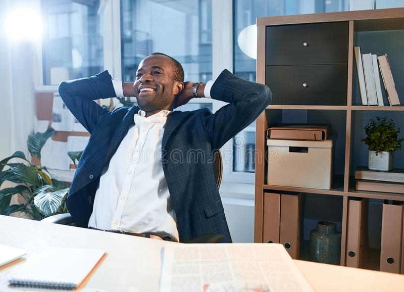 El hombre alegre confiado está disfrutando de su relajación en el trabajo fotos de archivo libres de regalías