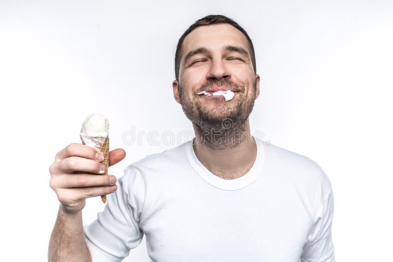 El hombre alegre y alegre está comiendo un helado no muy exacto sino con placer grande Aislado en el fondo blanco imagenes de archivo