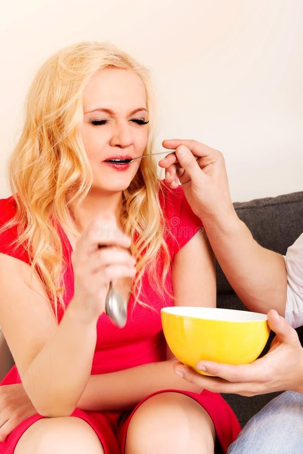 El hombre alimenta a su novia en el sofá imagenes de archivo