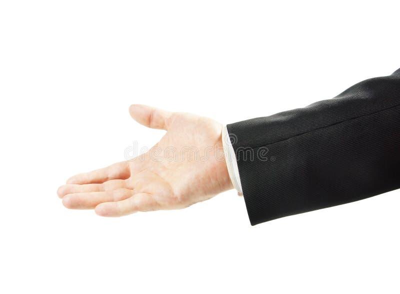 El hombre amistoso en un traje alcanza el suyo distribuye con una palma abierta para arriba aislada foto de archivo
