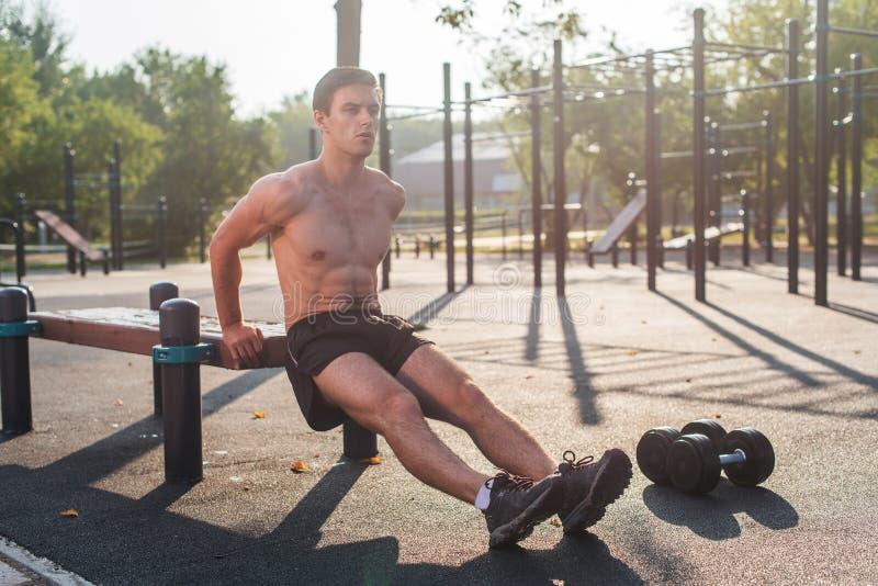 El hombre apto de los jóvenes que hace el tríceps sumerge ejercicios durante entrenamiento al aire libre del entrenamiento cruzad imagenes de archivo
