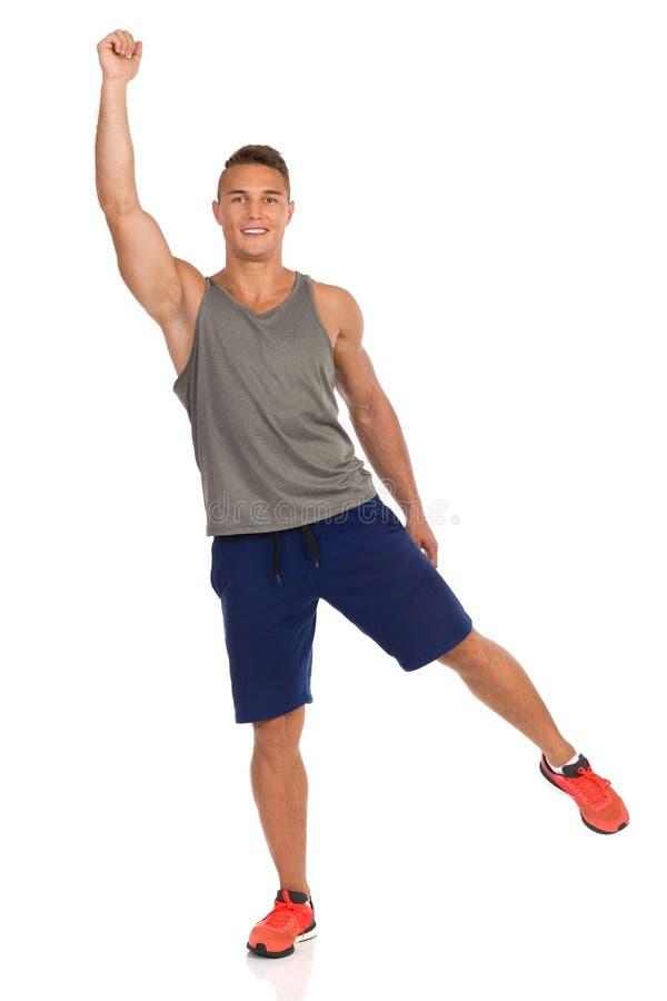 El hombre apto joven se est? colocando en una pierna con el brazo aumentado imagenes de archivo