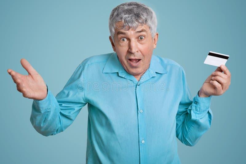 El hombre arrugado maduro desconcertado con las arrugas en la cara, pelo gris, hombros de los encogimientos de hombros en el desc fotos de archivo libres de regalías