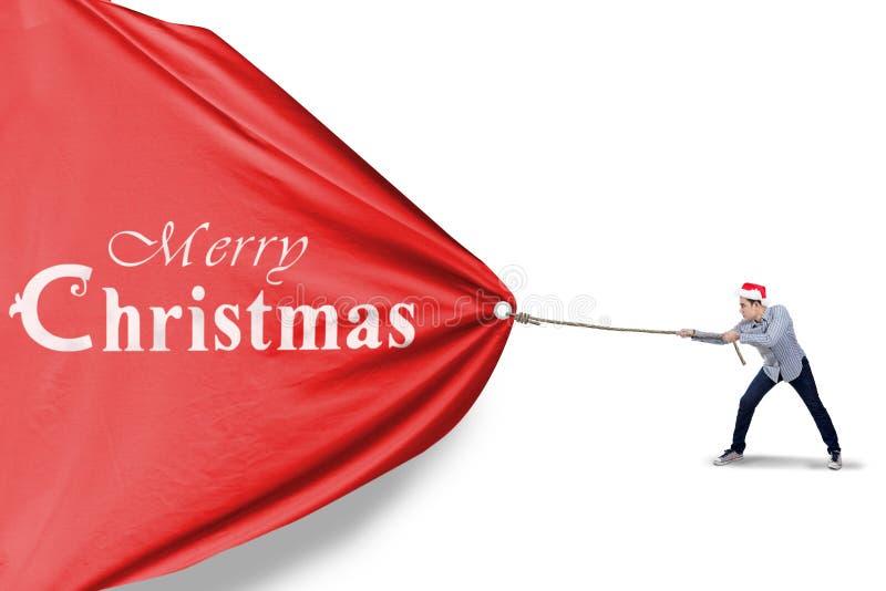 El hombre asiático está tirando de la bandera de la Navidad imagen de archivo libre de regalías